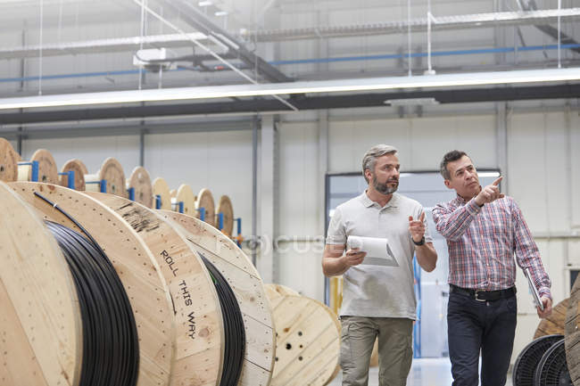Male supervisor and worker with clipboard walking along spools in fiber optics factory — Stock Photo