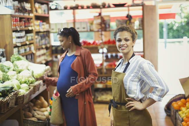 Porträt zuversichtlich Arbeitnehmerin im Lebensmittelgeschäft zu produzieren — Stockfoto
