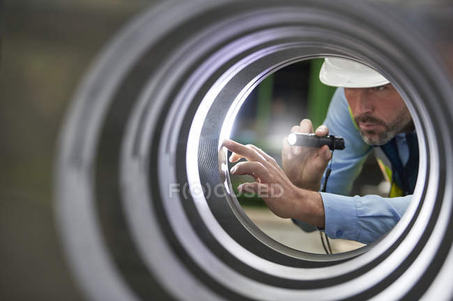 Male engineer with flashlight inspecting steel cylinder — Stock Photo