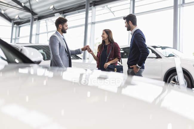 Venditore di auto dando le chiavi dell'automobile ai clienti nello showroom della concessionaria di automobile — Foto stock