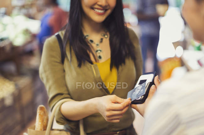 Young woman paying cashier with contactless credit card payment in store — Stock Photo