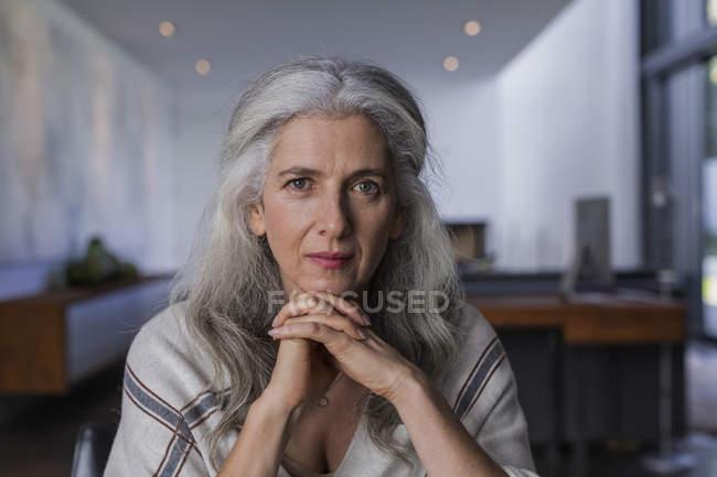 Portrait confiante, sérieuse femme d'âge mûr aux cheveux longs gris — Photo de stock