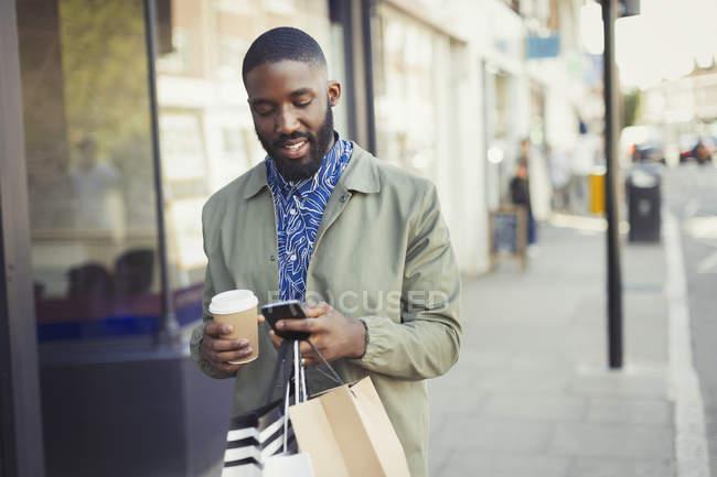 Jovem com mensagens de café e sacos de compras com celular na calçada urbana — Fotografia de Stock