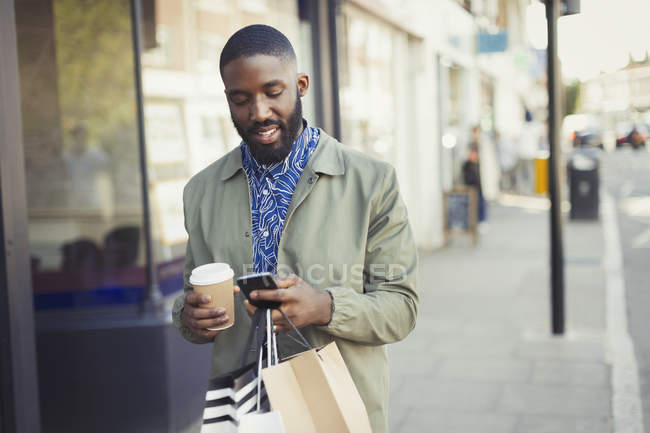 Young man with coffee and shopping bags texting with cell phone on urban sidewalk — Stock Photo