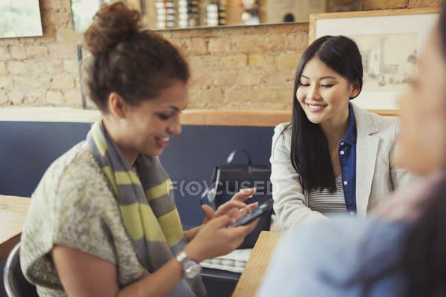 Freundinnen SMS mit Handy im café — Stockfoto