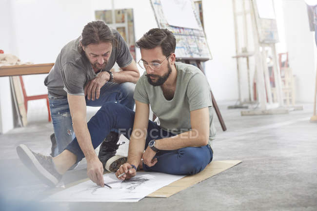 Male artists sketching on floor in art class studio — Stock Photo