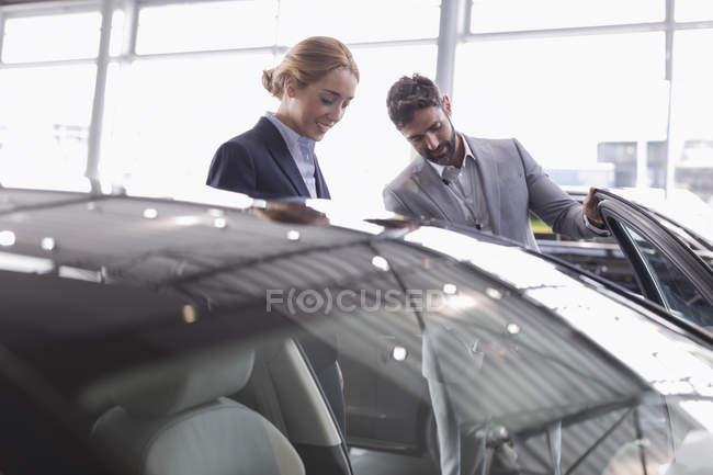 Продавець показ новий автомобіль жіночий клієнта в дилерському автосалон — стокове фото