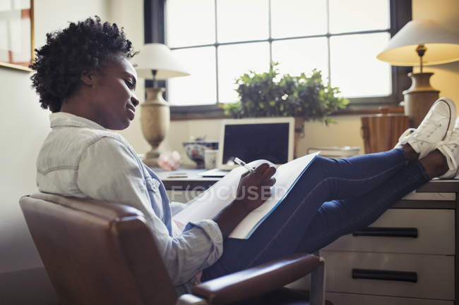 Businesswoman reviewing paperwork with feet up on desk — Stock Photo