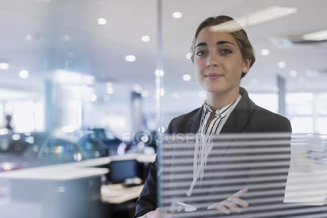 Portrait confident car saleswoman in car dealership showroom — Foto stock