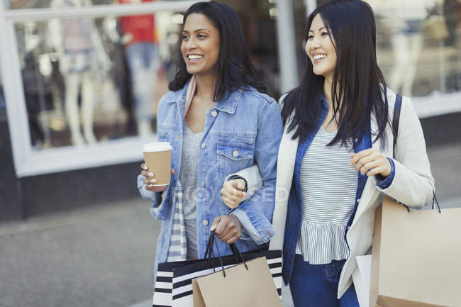 Smiling women friends walking arm in arm along storefront with coffee and shopping bags — Stock Photo