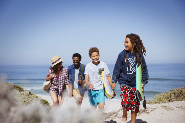 Multi-ethnic family walking with boogie boards on sunny summer ocean beach — Stock Photo