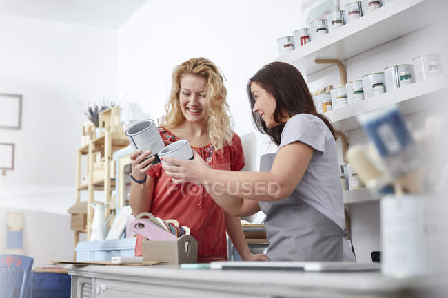 Улыбаясь женского бизнеса владельца, помогая клиенту выбрать краску в арт-магазин — стоковое фото