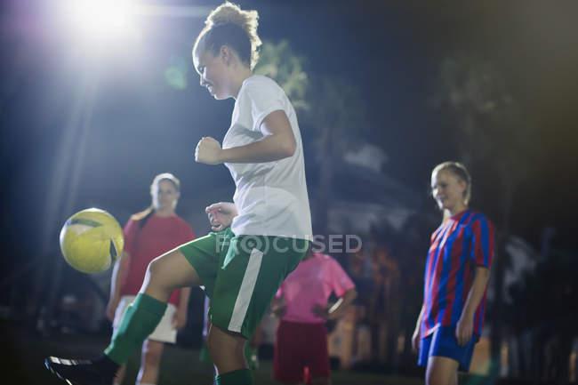 Junge Fußballerin kickt den Ball, übt nachts auf dem Feld — Stockfoto