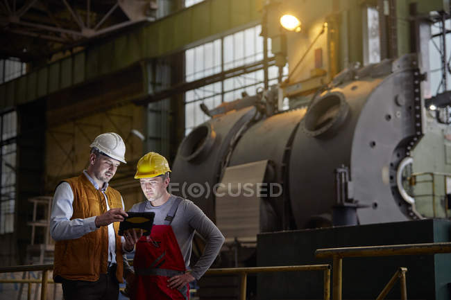 Male engineer and worker using digital tablet in dark factory — Stock Photo