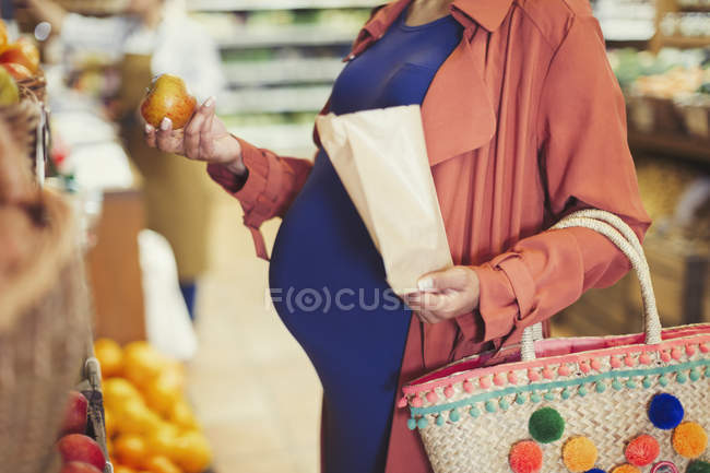 Pregnant woman shopping for apples in grocery store — Stock Photo