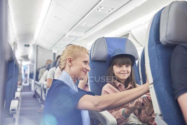 Flight attendant helping girl passenger on airplane — стокове фото