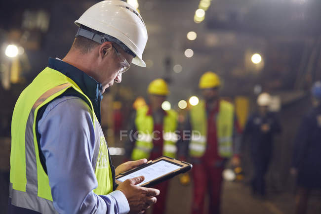 Steelworker using digital tablet in steel mill — Stock Photo