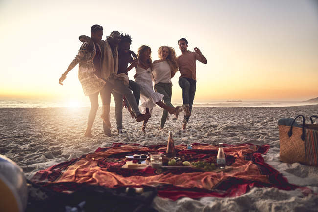 Playful young friends kicking, enjoying picnic on sunny summer sunset beach — Stock Photo