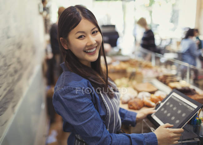 Portrait smiling, confident female cashier at cash register in cafe — Stock Photo