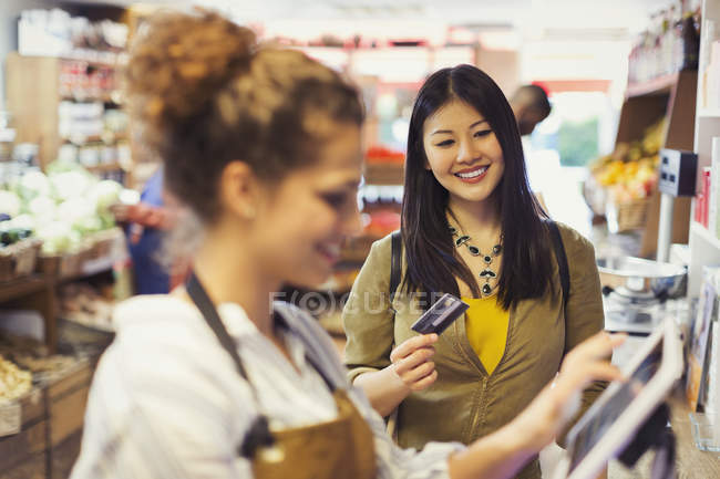 Smiling female shopper with credit card paying cashier at grocery store cash register — Stock Photo