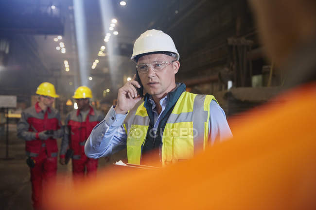 Steelworker supervisor talking on smart phone in steel mill — Stock Photo