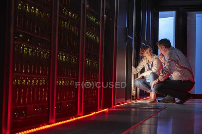 Он техников, говоря на светящиеся панели в темных серверной комнате — стоковое фото
