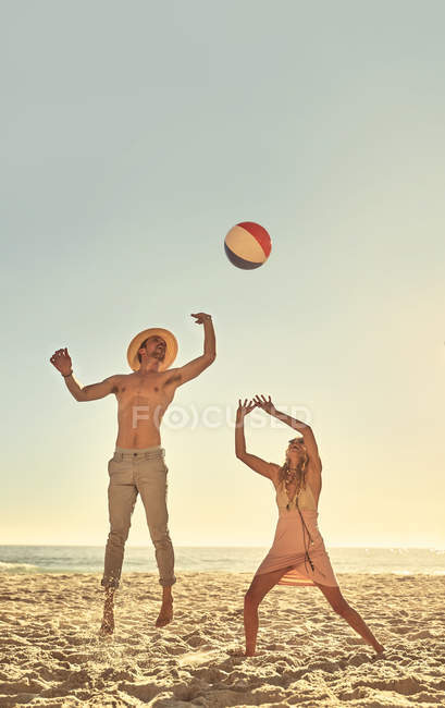 Young couple playing with beach ball on sunny summer beach — Stock Photo