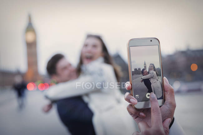 Personal perspective, playful couple hugging and being photographed with camera phone near Big Ben, London, UK — Stock Photo