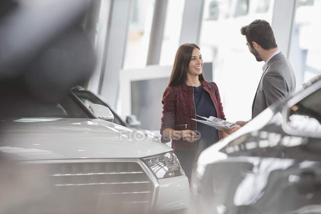 Автомобіль Продавщиця показ Брошура для чоловічого клієнта в дилерському автосалон — стокове фото