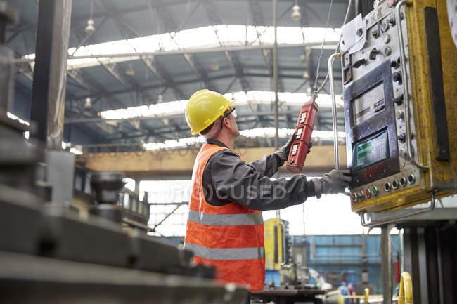 Macchine operatrici maschili presso il pannello di controllo in fabbrica — Foto stock