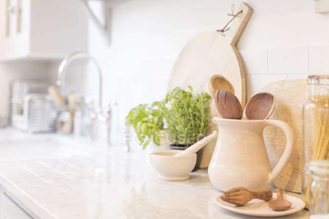 Cuillères en bois nature morte au pichet sur le comptoir de cuisine — Photo de stock