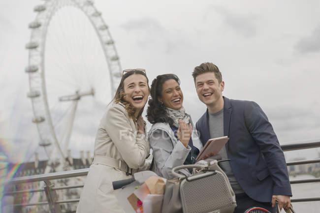 Portrait laughing friends with digital tablet near Millennium Wheel, London, UK — Stock Photo