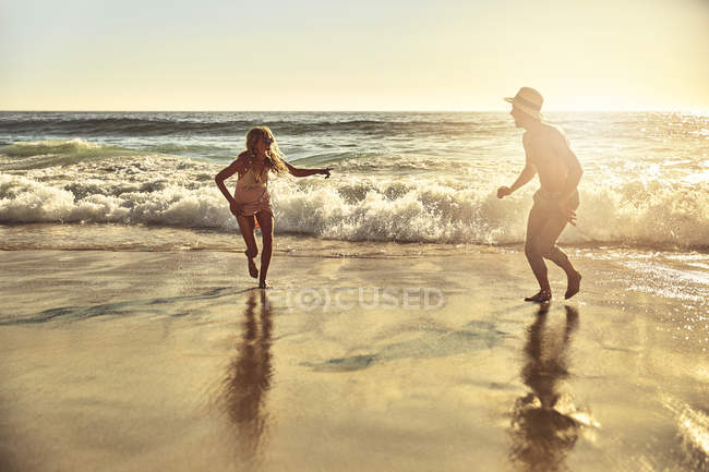 Playful young couple running in wet sand on sunny summer ocean beach — Stock Photo
