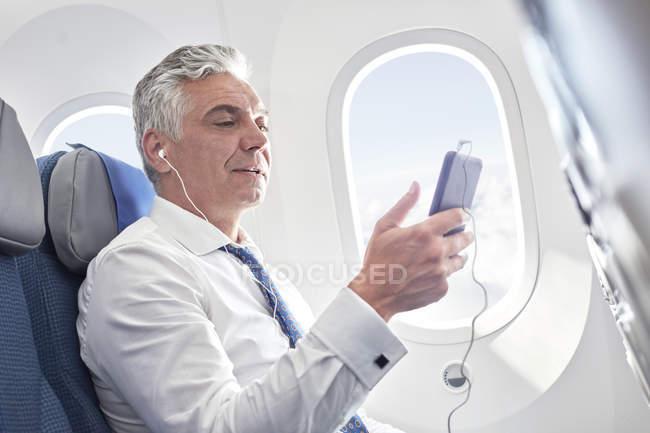 Empresário ouvindo música com fones de ouvido e mp3 player no avião — Fotografia de Stock