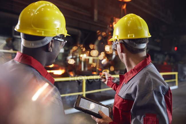 Supervisor and steel worker with digital tablet working in steel mill — Stock Photo