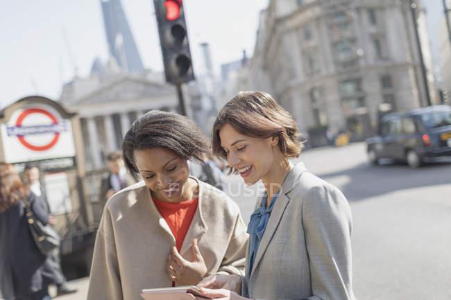 Smiling businesswomen with digital tablet talking on sunny urban city street — Stock Photo