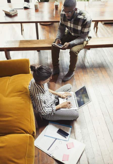 Женщина-фрилансер работает за ноутбуком на полу в гостиной — стоковое фото