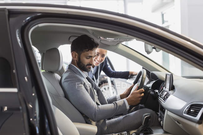 Car saleswoman and male customer in driver?s seat of new car in car dealership showroom — Stock Photo