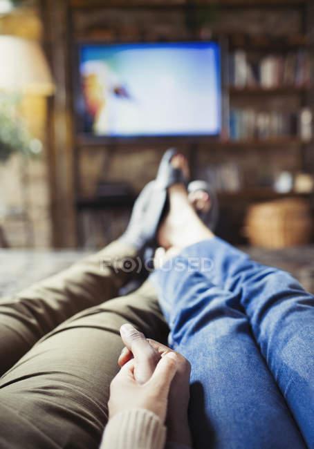 Особистої точки зору ласкавим пара холдингу руки дивитися телевізор у вітальні — стокове фото