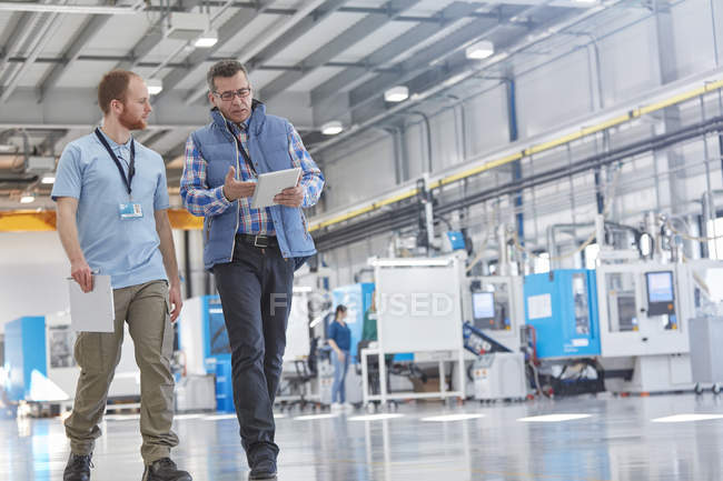 Male supervisor and worker with digital tablet talking and walking in factory — Stock Photo