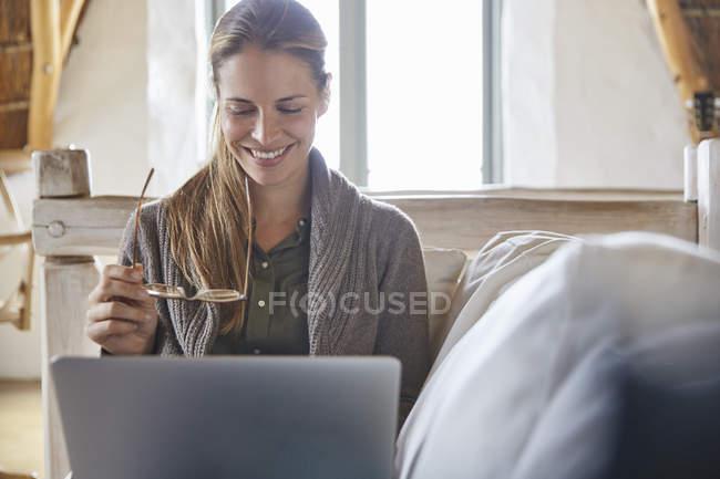Femme souriante avec lunettes à l'aide de portable sur canapé — Photo de stock