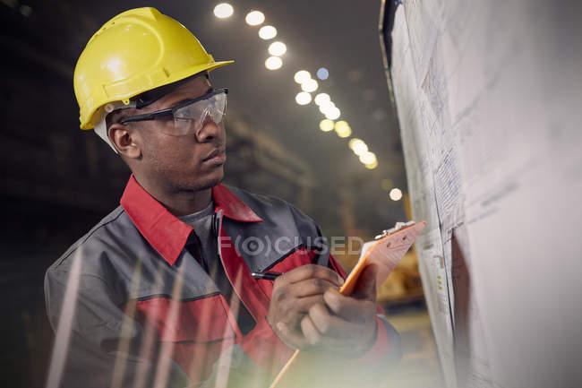 Fokussierter Stahlarbeiter mit Klemmbrett an Informationstafel im Stahlwerk — Stockfoto
