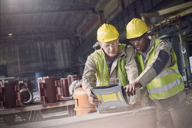 Two steelworkers using laptop in steel mill — Stock Photo