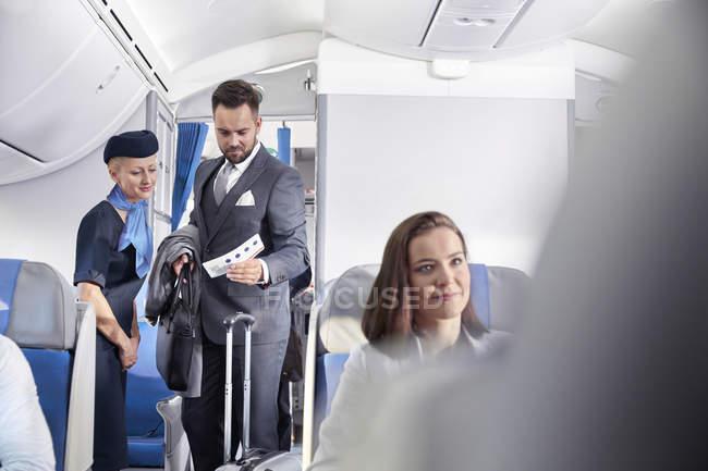 Asistente de vuelo ayudando a hombre de negocios con tarjeta de embarque en el avión - foto de stock