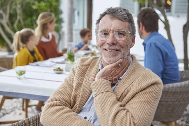 Porträt lächelnder älterer Mann genießt Mittagessen mit Familie — Stockfoto