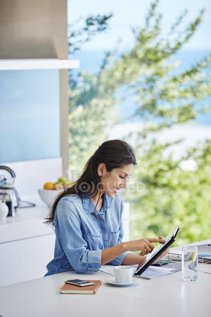 Frau arbeitet mit digitalem Tablet an Küchentheke — Stockfoto