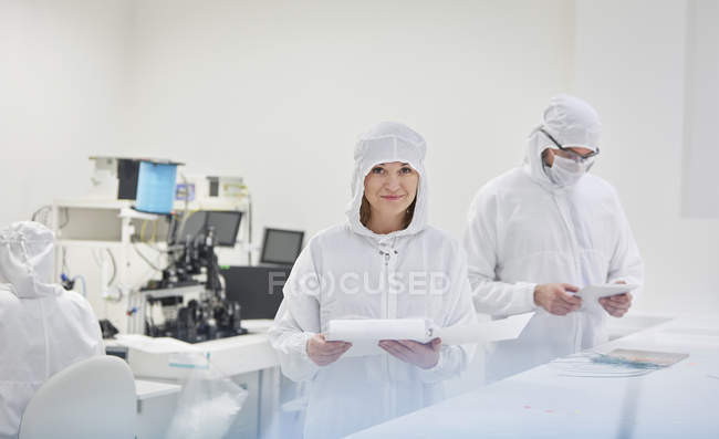 Portrait smiling female engineer in protective suit with paperwork in fiber optics research and testing laboratory — Stock Photo