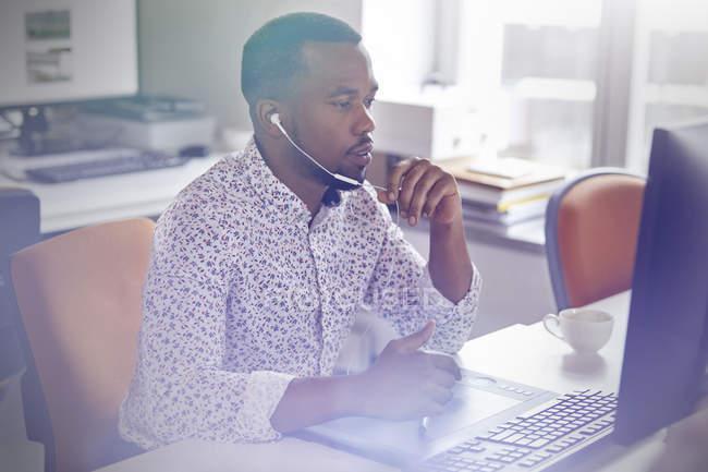 Progettista grafico maschio lavorando al computer in tavoletta grafica, ne il telefono con le cuffie — Foto stock