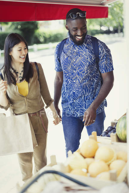 Young couple shopping for produce at market storefront — Stock Photo
