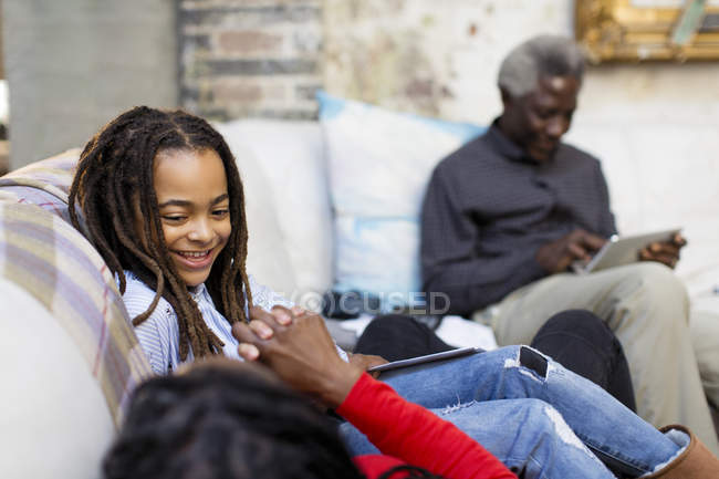 Lächelndes Mädchen entspannt sich mit Familie auf Sofa — Stockfoto